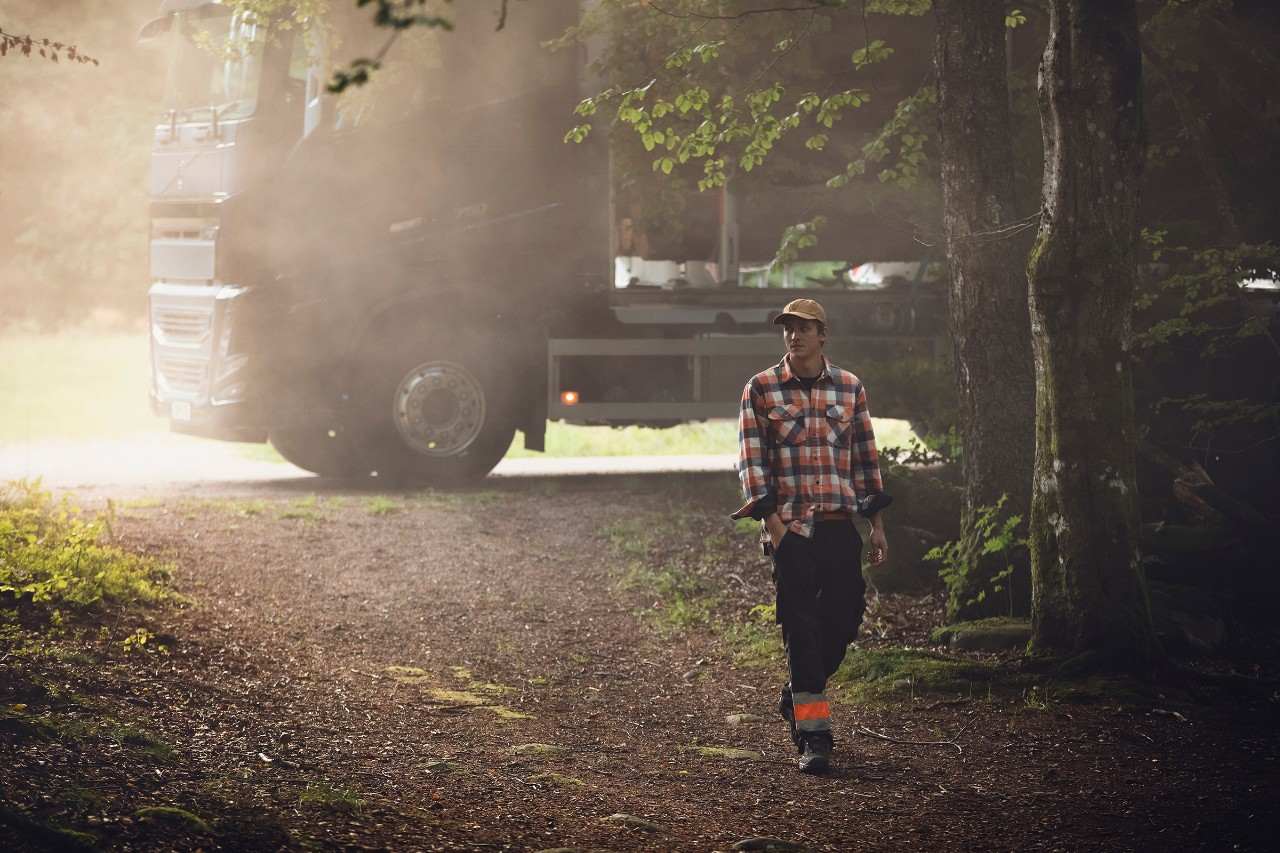 A truck parked behind a man walking through a forest