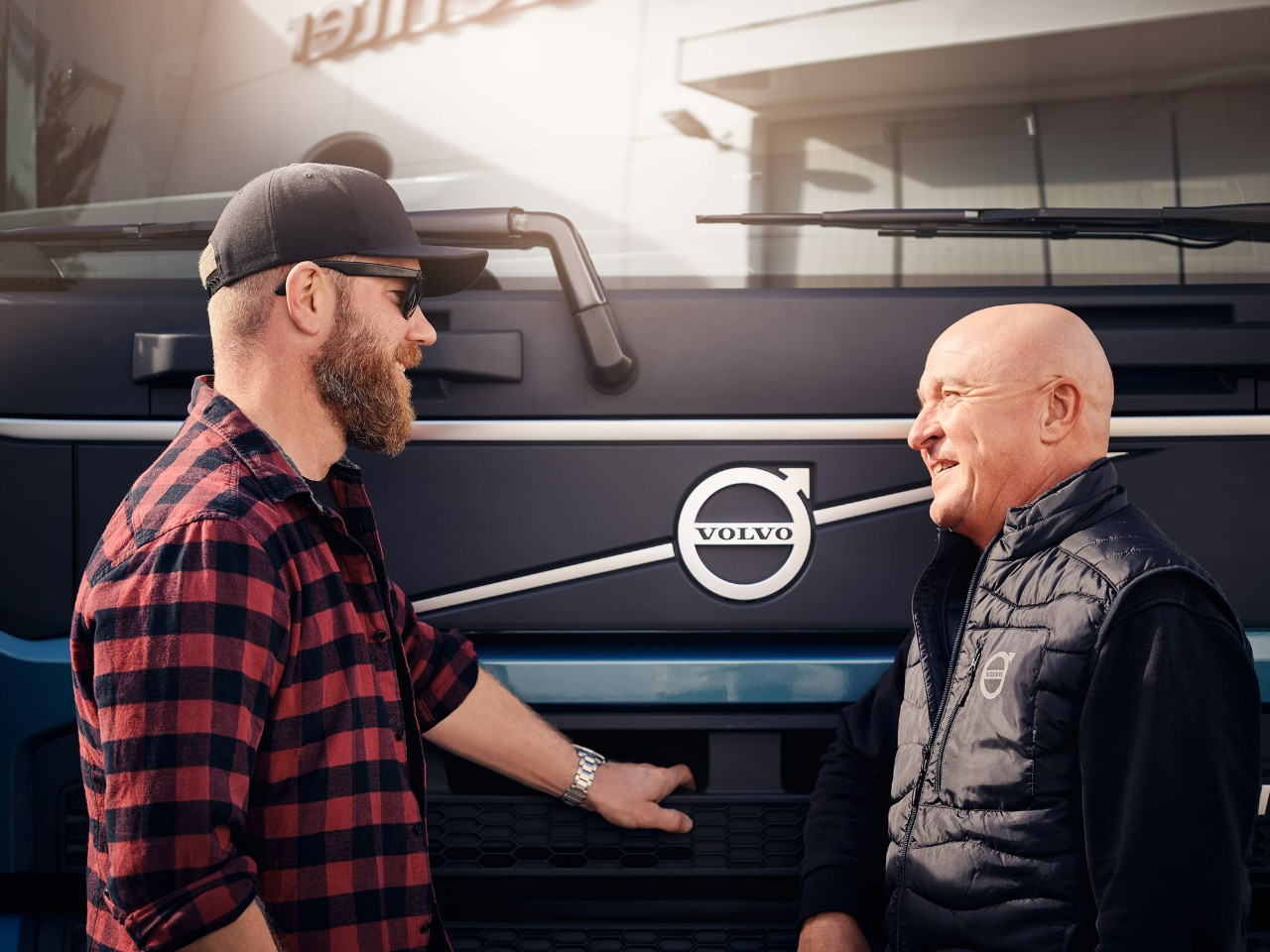 Two men speak in front of a Volvo truck