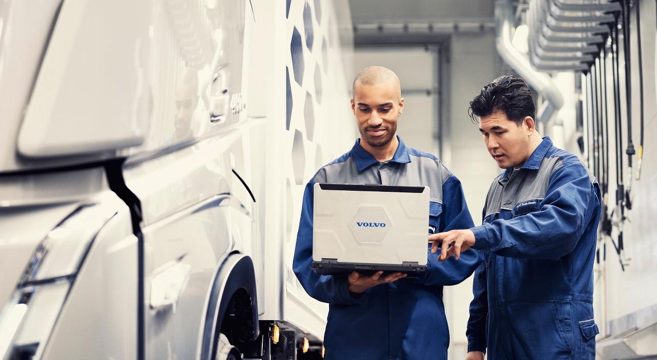 Двама сервизни механици на Volvo гледат лаптоп, докато стоят до товарен автомобил