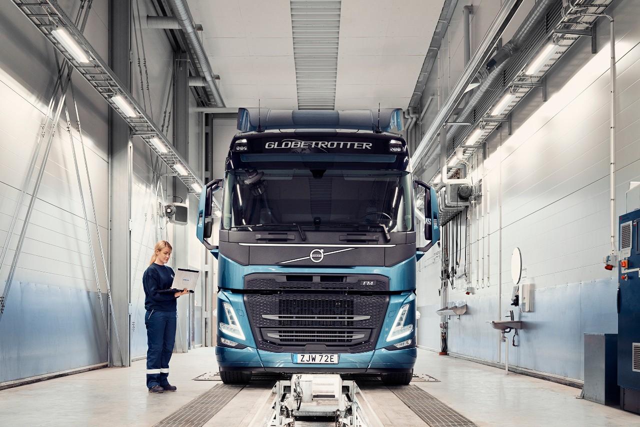 Сервизен техник на Volvo държи компютър, докато стои до товарен автомобил